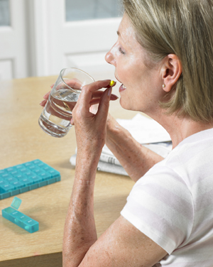 Woman sitting at table taking pill, holding glass of water. Pill organizer is on table.