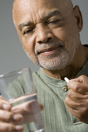 Man holding pill and glass of water.