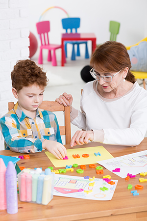Therapist helping boy learn the alphabet.