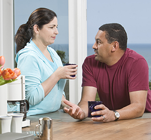 Man and woman in kitchen talking.